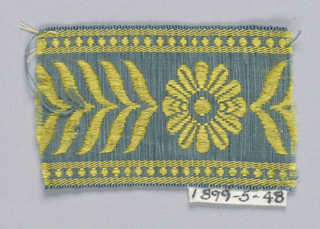 Flower and chevron-like leaves in yellow on blue.
