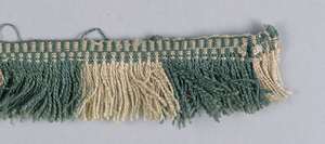 Green and tan fringe with a patterned heading and skirt threads arranged to form colored stripes.