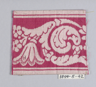 Curving scroll with flower in white on red.
