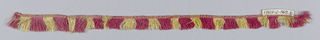 Red and yellow fringe with a decorative heading and skirts threads arranged to form stripes.