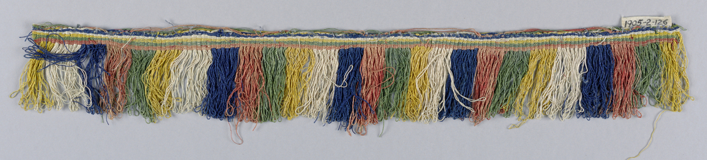 Fringe with a blue, red, green, yellow and white striped heading. Skirt threads, looped and twisted, are arranged to form stripes.
