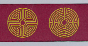 A row of eleven labyrinths woven to be reversible in gold color and dark red.