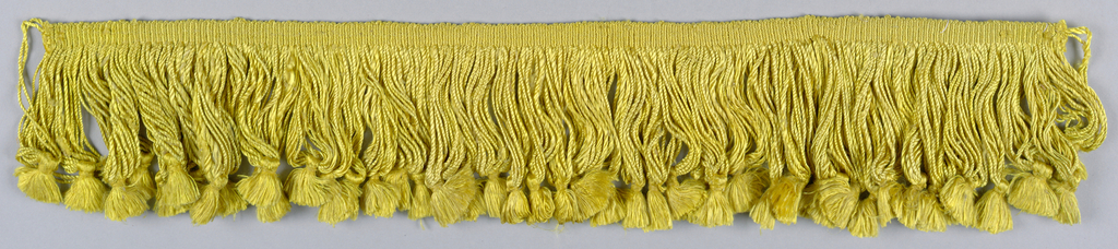 Yellow fringe with a heading and looped skirt threads; each group of eight loops supports a tuft.