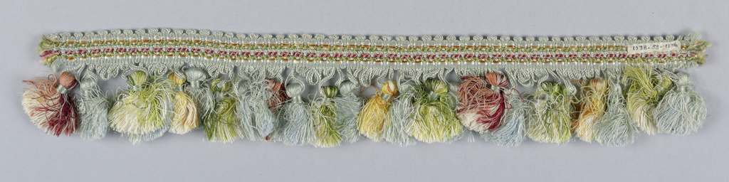 Trimming has a woven header finished with loops and tassels. Color are primarily light blue with green, red, yellow, orange, and white.