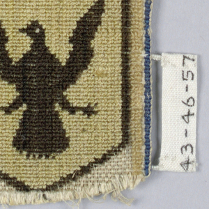 """Two shields, each under a crown, one displaying arms with motto, """"Vis mea est lex et rex."""" (Trans. """"My strength is law and king."""")  The other, a spread eagle, in black, yellow, and tan on a white ground."""