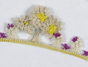 Trimming of white flowers with yellow and pink centers.