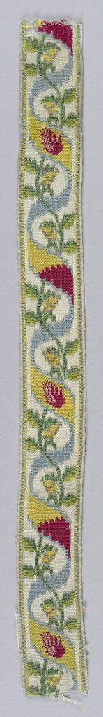 Design of a serpentine flowering stem entwined with colored ribbon. In blue, dark yellow, dark red and olive green on a white ground. Narrow striped borders in blue and dark yellow.