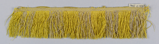 Fringe with a yellow and tan plain-woven heading. Skirt threads of yellow and tan are looped and twisted.