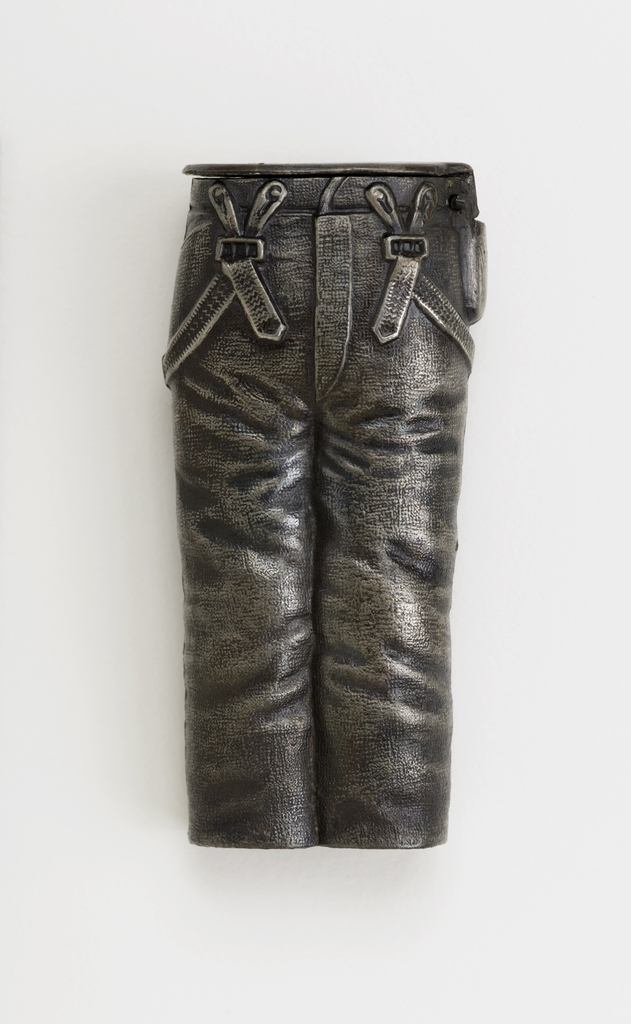 In the form of a pair of trousers with creases, back pocket, suspenders draped over hips, tool pouch on right hip, overall surface textured to simulate fabric. Flat, flip top lid hinged above tool pouch. Striker on bottom.