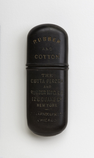 """Elongated oval matchsafe in a dark brown color. One side says """"Rubber and Cotton The Gutta Percha & Rubber MFG. CO. 126 Duane St. New York Randolf St. Chicago"""". The reverse side has a cross and says """"Fire Hose hose belting packing vaulves & co."""""""