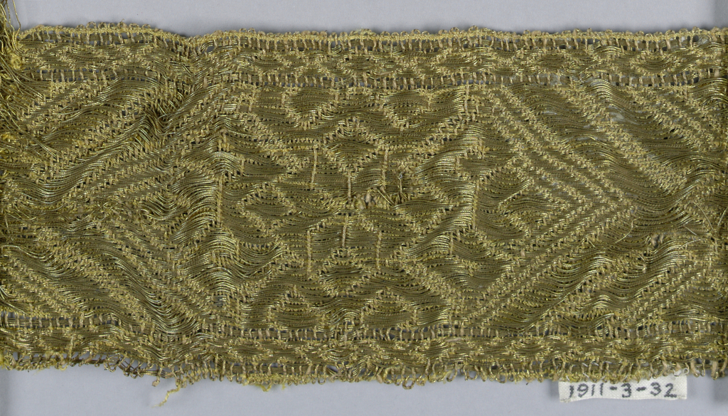 Yellow silk and gilt thread trimming fragment in a design of angular scrolls and leaves within hexagons.