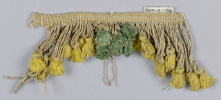 Yellow and green fringe with a heading and looped skirt threads holding tufts arranged to form a pointed edge.
