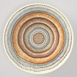 Round plate decorated with undulating concentric circles in blue and earth tones.