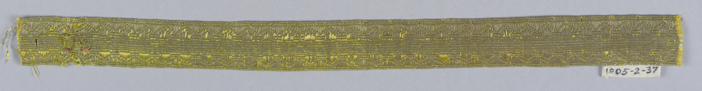 Design of a ribbed center with saw tooth borders in yellow and metallic thread.