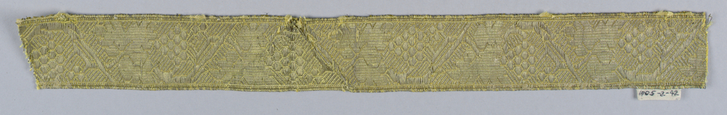Design of a vine with grapes and fruit in an angular arrangement. In yellow and metallic thread.