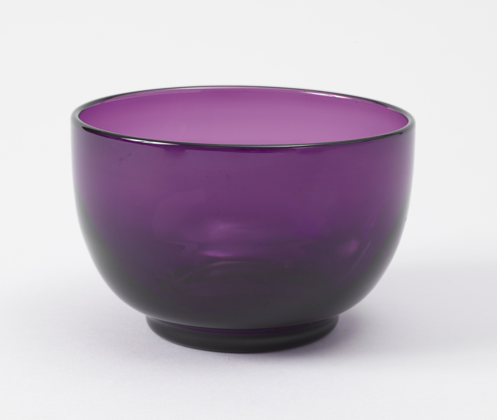 Plain bowl of aubergine-colored glass, probably intended as inset in cut-out silver piece.