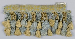 Galloon with attached fringe. Galloon has a yellow flower and leaf design on a blue ground. Attached fringe has a heading and looped skirt threads in two lengths. Each four loops supporting a tuft.