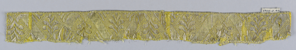 Design of leaves placed alternately up and down with diagonal bands in between. In yellow and white with silver metallic thread.