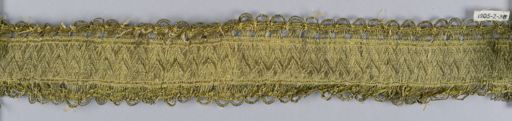 Design of saw tooth bands with an open weave forming scalloped borders. In yellow and metallic thread.