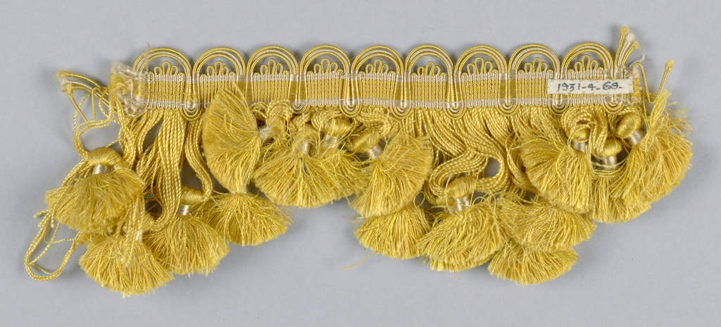 Yellow fringe with tasseled ends arranged in scallops. Corded top in yellow and white.
