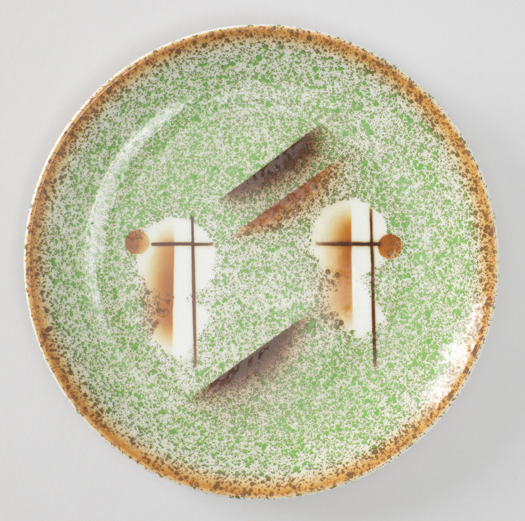 Round plate with a splotchy brown rim and splotchy green center. There are two symmetrical circle and line designs in the center of the plate.