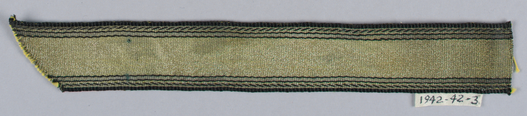 Gold and black with warps of gold and black threads. Weft is yellow silk. The design consists of black stripes along each side with a diagonal pin stripe just within the final black edging.