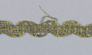 Design with loops on both edges formed by carrying down the heavy wefts. In yellow silk and metallic thread.