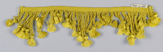 Yellow fringe with a heading and looped skirt threads forming a pointed edge; each group of four supporting a tuft.