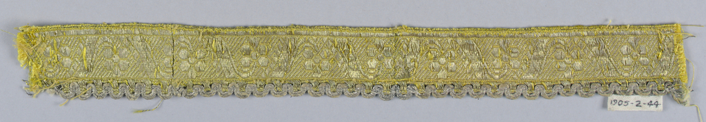 Design of flowers placed alternately up and down with diagonal bands in between. On one edge, a border in an open weave forming scallops. In yellow and white with silver thread.