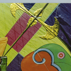 View of many colorful kites from above. In white ink, lower right: go fly / a kite.
