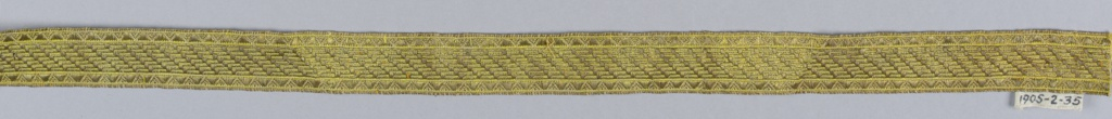 Design of saw tooth borders with broken diagonal lines between. In yellow and metallic thread.