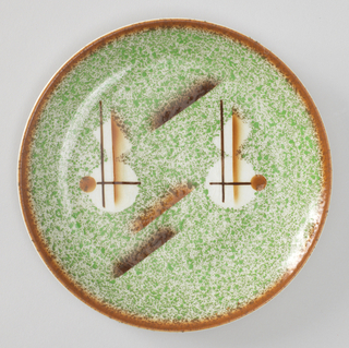 Round plate with a splotchy brown rim and splotchy green center. There are two 