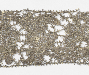 Metallic, two different thicknesses of silver-wrapped thread making a floral design.