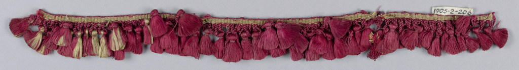 Red fringe with a heading and small loops supporting tufts of floss.