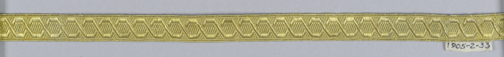Angular guilloche design in yellow and metallic thread.