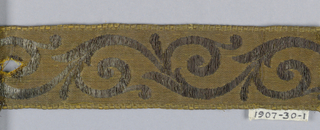 Trimming (galloon) with design of scrolls in silver on gilt ground; furnishing trim.