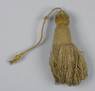 Tassel with a skirt of gold-colored silk threads partly covered by a trellis of twisted threads of same color; collar of cut threads topped by a knob covered with silk threads in twill pattern. Cord of braided silk threads.