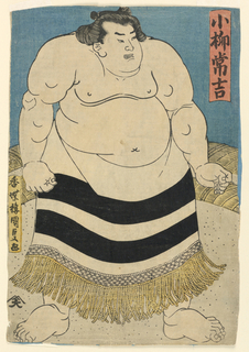 Full length figure of a sumo wrestler, wearing a horizontally striped skirt with fringe edge.