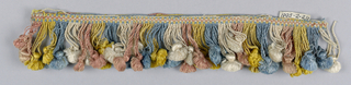 Blue, white, pink and yellow fringe with a checkboard heading and looped skirt threads supporting a tassel of the same color.