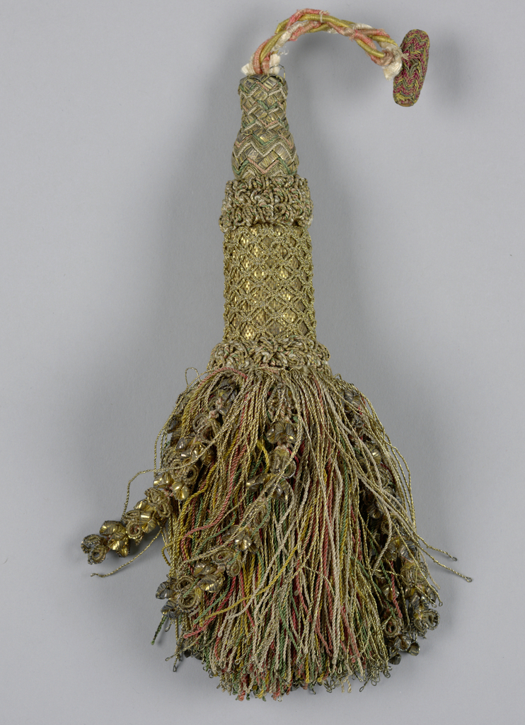 Tassel with a turned wooden core covered with metal foil, metallic thread, and silk in a woven and knotted pattern; skirt of twisted silk threads (green, white, yellow, and pink) covered with threads and strings of flower-like forms in metal. Cord at top of yellow, pink and white threads with cylinder covered with pink, yellow and gold threads in chevron pattern.