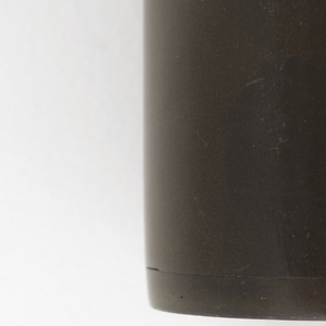 A cylindrical matchsafe in a dark brown color with two stripes around the side. On the top there is company logo and an image of an animal in an outdoor scene.