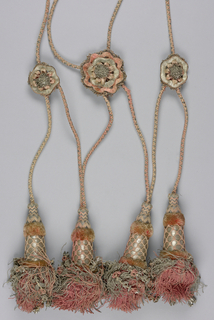 Each has four large tassels hanging from lattice arrangement of thick plaited silk cords, clasped by three large decorated rosettes half way up and by two smaller ones at the top. Tassels (20 cm long) have deep tops with tufting border and silk lattice over silver thread wound on woven core. Pink silk; silver; silver metal threads.