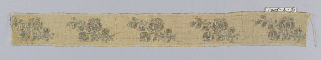 Design of detached flowering sprays in silver thread on a silk ground. In pink and silver.