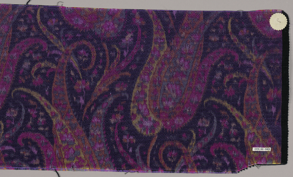 Heavyweight silk with horizontal ribbing has a tightly-spaced allover multicolored design with a paisley-cone motif surrounded with many small floral forms. Colors are primarily shades of pink with orange, yellow, and blue-grey on a dark purple ground. Right selvedge present.