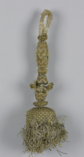 Tassel with a skirt of white silk partly covered by trellis of metallic thread. The cord which runs through the tassel carries seven ornaments, each one of wood covered with silk and metallic thread in a chevron pattern and one with knots. Wooden core covered with white linen plain cloth.