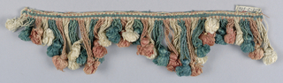 Pink, green and white fringe with a striped heading and skirt loops in graduated lengths forming scallops; each four supporting a tuft of the same color.