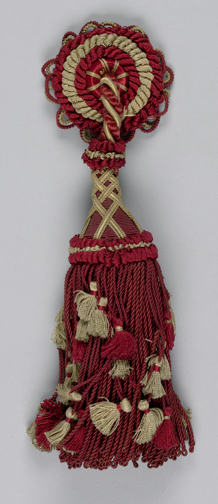 Tassel with a skirt of red silk twisted and looped with small red and tan tassels in outer strands. Tassel head of red silk with tan braid forming crosses and two collars of red and tan silk in loops. Tassel is attached by a cord to a rosette which is composed of a central button surrounded by rings of red and tan silk loops.