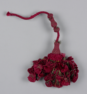 Skirt of strings of silk with tassels and ornaments of red silk and silver thread. Collar of red silk, head of two balls, and two vase-shaped parts covered with red silk and metal thread in a triangular design and strung on a red silk cord.