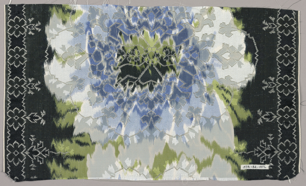 Chiné-printed ribbon has large-scale overlapping vertical blossoms in blue, grey and white on a black ground. Over these blossoms are woven stylized symmetrical floral forms and small-scale rosettes that create narrow side borders.