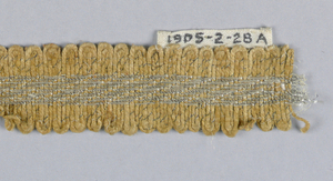 Band with a design of a silver ornament in the center and a scalloped edge formed by the manipulation of the weft.